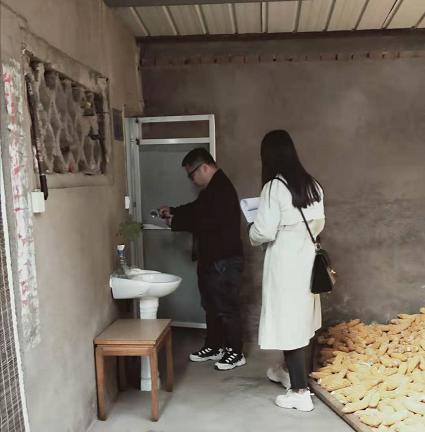 工作人员实地查看户厕硬件设施是否安装到位.png